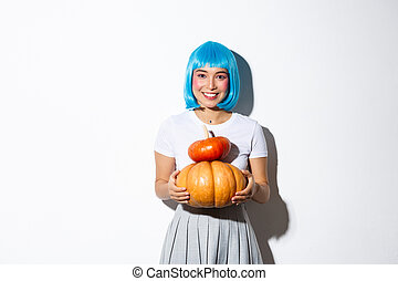 Adorable asian woman in blue wig holding two cute pumpkins and smiling at camera, wearing schoolgirl outfit for halloween party.