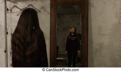 Adorable asian woman looking at herself in mirror