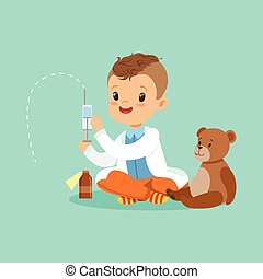 Adorable baby boy dressed as a doctor playing with teddy bear toy. Kid preparing syringe for his sick patient