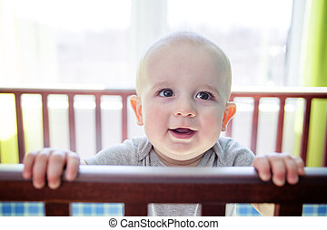 Adorable baby boy in his crib