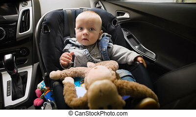 Adorable baby boy in safety car seat. He looks at the world with his huge blue eyes, around the toys.