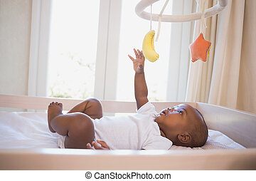Adorable baby boy lying in his crib playing with mobile