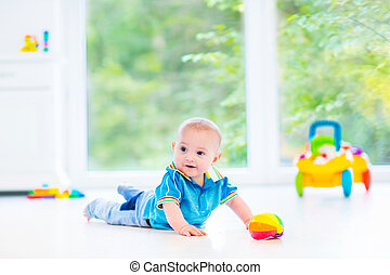Adorable baby boy playing with a colorful ball and toy car