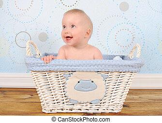 adorable baby boy sitting in blue wicker basket