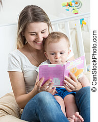 Adorable baby boy sitting on mothers lap and reading book