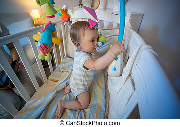 Adorable baby boy standing in crib and playing with toy carousel
