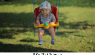 Adorable baby boy with big beautiful eyes having fun on a swing ride at a playground in a sunny summer park