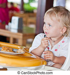 Adorable baby eating cake in a chair