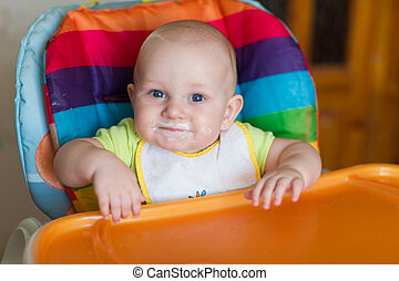 Adorable baby eating in high chair