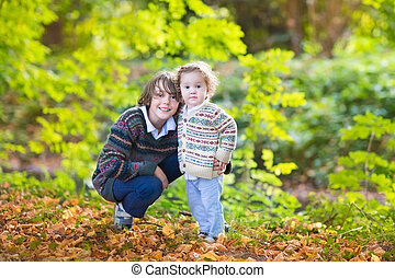 Adorable baby girl and her teen age brother playing together in