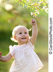 Adorable Baby Girl at Sunset Reaching for Flower in Tree
