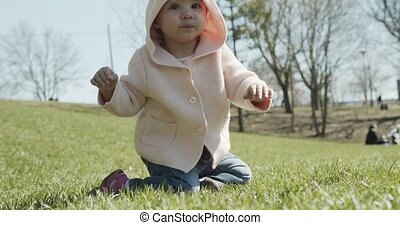 Adorable baby girl at the park dressed as a bear. Cinematic...