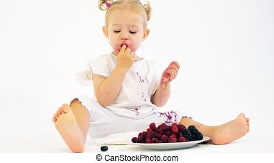Adorable baby girl eating fresh juicy berries on white...