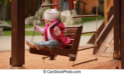 Adorable baby girl enjoying a swing ride on a playground in the city park.