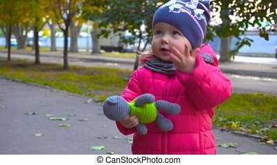 Adorable baby girl holding toy in autumn city - Adorable...