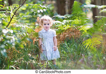 Adorable baby girl in a white dress playing in a beautiful sunny