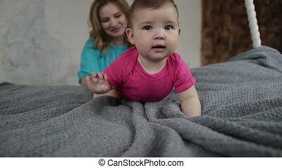Adorable baby girl learning to crawl on bed