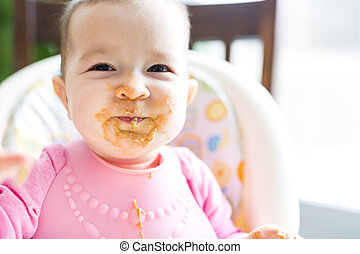 Adorable baby girl making a mess while feeding herself - An...