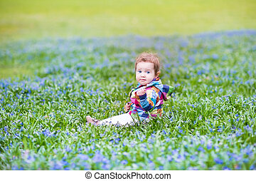 Adorable baby girl playing in a garden with lots of blue flowers