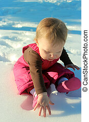 Adorable baby girl playing in snow