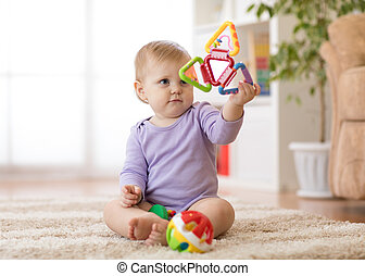 Adorable baby girl playing with educational toys in nursery.