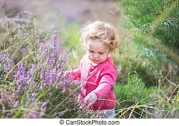 Adorable baby girl playing with purple flowers in a heather land
