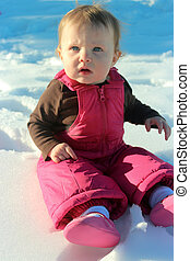 Adorable baby girl sitting in snow