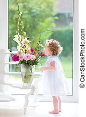 Adorable baby girl smelling flowers - Adorable baby girl...