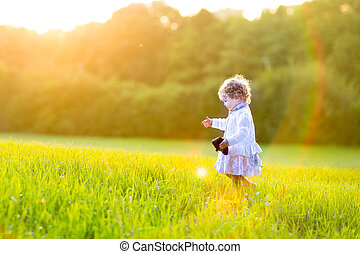 Adorable baby girl walking in an autumn field at sunset