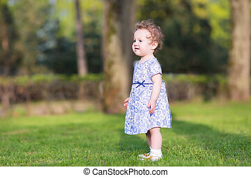 Adorable baby girl walking in the garden