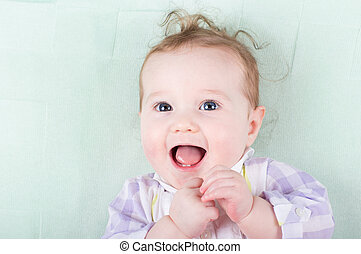 Adorable baby girl with funny curly hair laughing happily