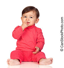 Adorable baby girl with her hand in mouth sitting
