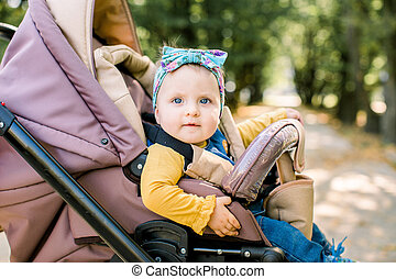 Adorable baby in child safety seat on white background