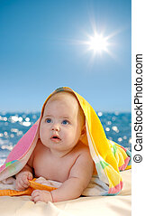 Adorable baby in colorful towel on sea beach