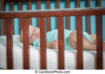 Adorable baby in his crib - An Adorable baby boy in his crib
