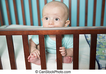 Adorable baby in his crib