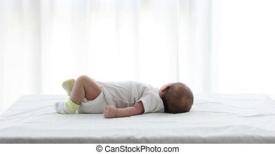 Adorable baby lying on back white background