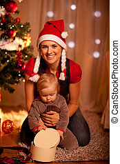 Adorable baby near Christmas tree opening Christmas gifts with mother