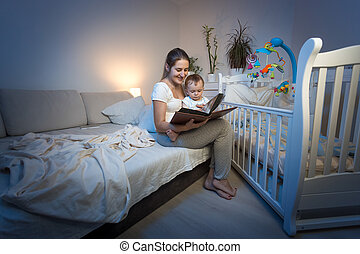 Adorable baby sitting on mothers lap and reading book before going to sleep