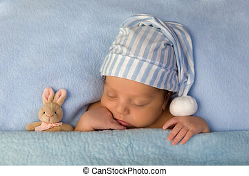 Adorable baby sleeping in blue bed