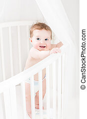 Adorable baby wearing a diaper standing in a white round crib