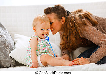 Adorable baby with soother and young mother playing on divan...