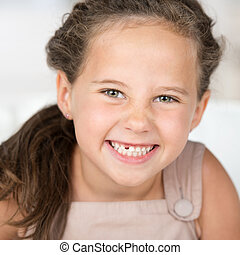 Adorable beautiful little girl grinning at the camera ...