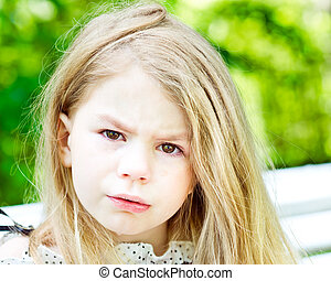 Adorable blond crying little girl with tears on her cheeks