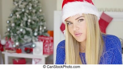 Adorable blond girl in christmas hat in her home