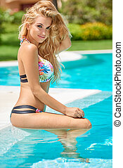 Adorable blond girl sitting in swimming pool