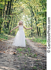 adorable blond girl walking in sunny day in magical forest