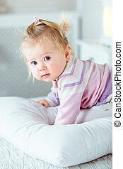 Adorable blond little girl with big grey eyes and plump cheeks