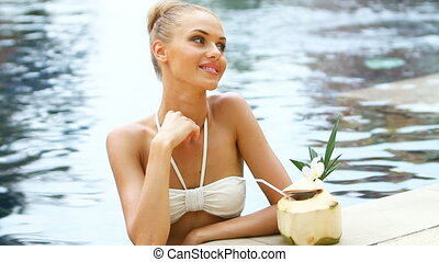 Adorable blond woman standing in swimming pool and drink...