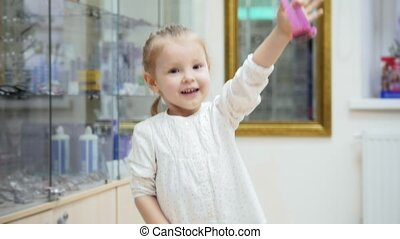 Adorable blonde Girl dancing and asks mommy to buy pink glasses in medical store - shopping in clinic